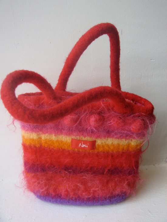 A small felted bag with stripes in reds, pinks, and yellows sits against a white background. It has soft, felted handles.