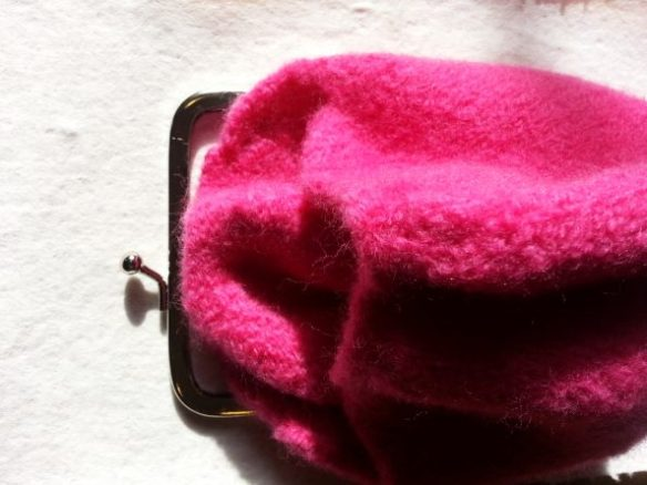 A hot pink felted purse is lined up with the purse frame it needs to be sewn into.