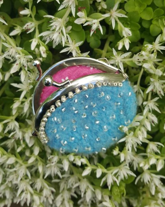 A tiny felted purse made in light blue wool with hand beading has a fun pink lining. The purse is lying on a bed of sedums that are bright green with white flowers.