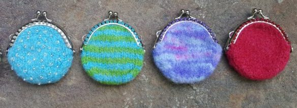 "A series of tiny Noni ""A Bit of Hope"" Felted bags are lined up vertically."