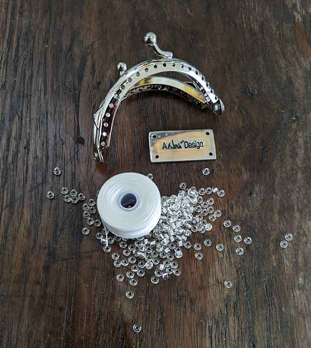 A tiny purse frame, a spool of white thread, silver-lined clear seed beads, and A Noni Design Label comprise the Little Bit Of Hope purse hardware kit displayed here on a wooden surface.