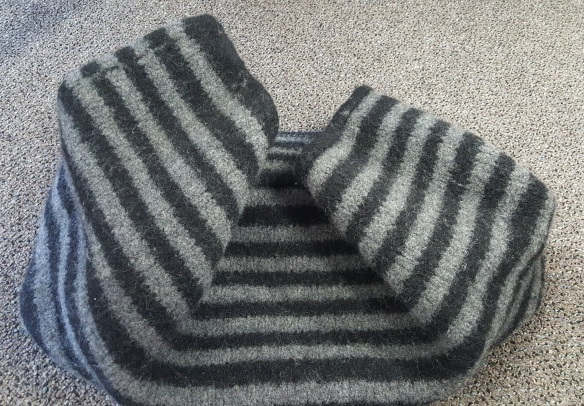A grey and black striped felted bag body after felting but before finishing is lying on a grey background.