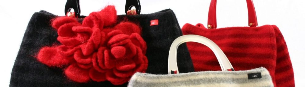Three felted bags are arranged on a white background: a large black one with huge red flowers, a medium sized bag in red stripes, and a small sized bag in white and grey stripes.