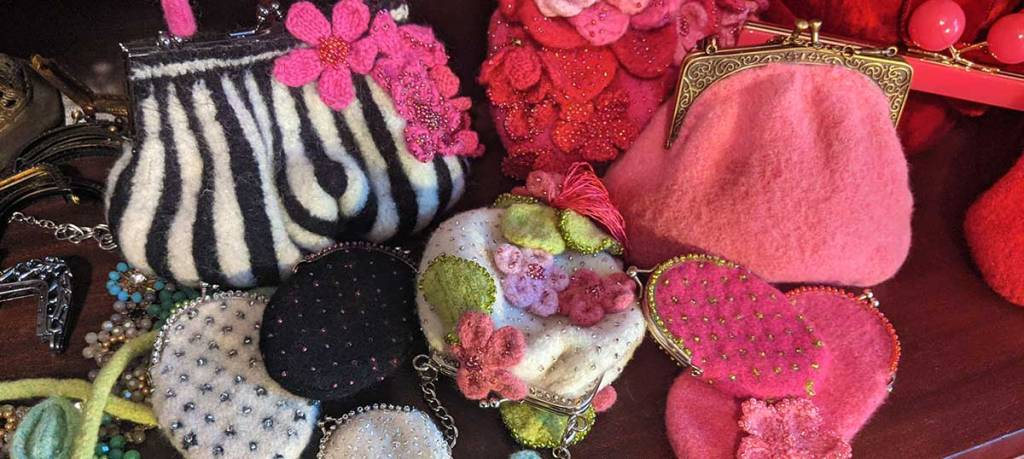 An array of Nonibags are arranged together on a wooden surface: a black and white purse with pink flowers, a small white purse, a poofy pink purse, a purse with lots of pink and red flowers, etc.