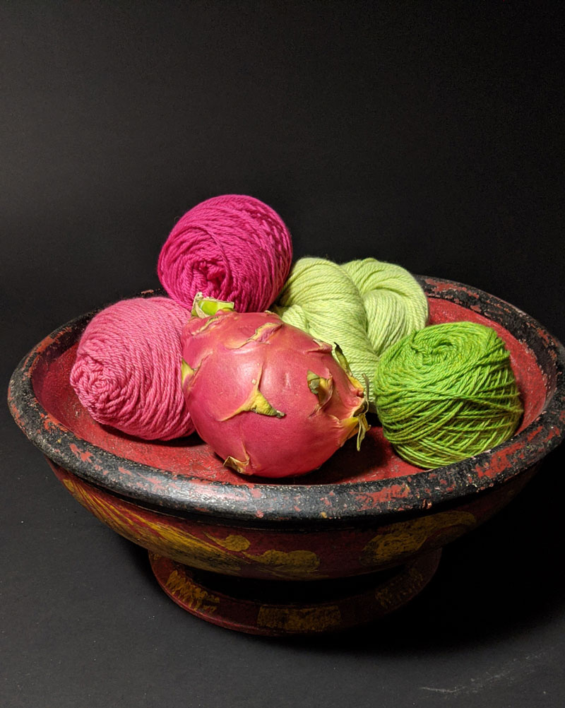 A red dragon fruit sits in a bowl with balls of hot pink, zinnia pink, light green, and medium green balls of yarn.
