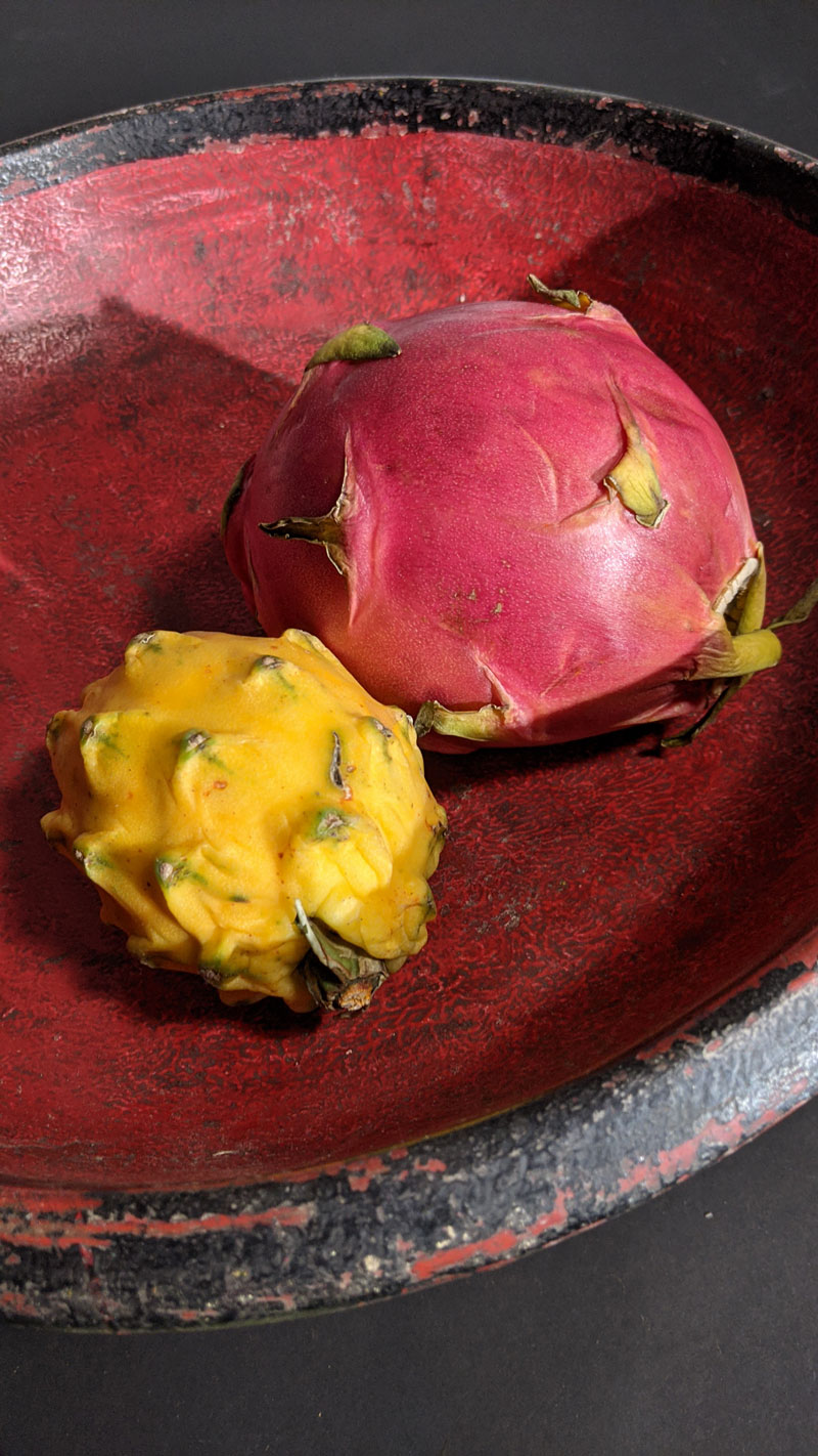 Yellow and red dragon fruits are sitting in a red bowl.