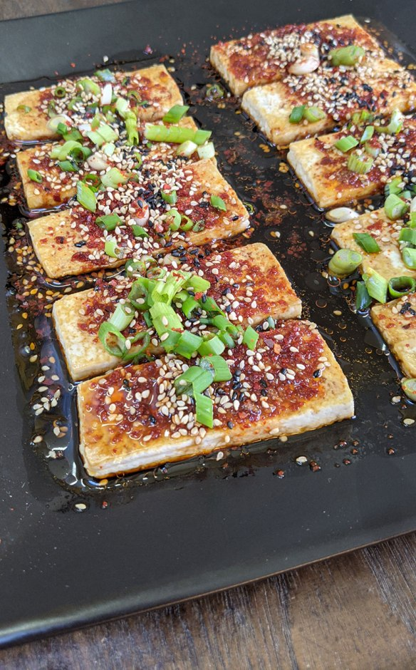 A plate of Dubu Jorim: Slices of fried tofu are lined up on a black plate and then drizzled with spicy sauce and sprinkled with fresh scallions and sesame seeds.