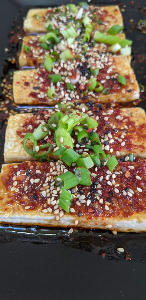 Slices of tofu are lined up on a black plate and drizzled with a spicy Korean sauce of soy sauce, sesame oil, and chilli flakes to make Dubu Jorim, a classic Korean side dish.