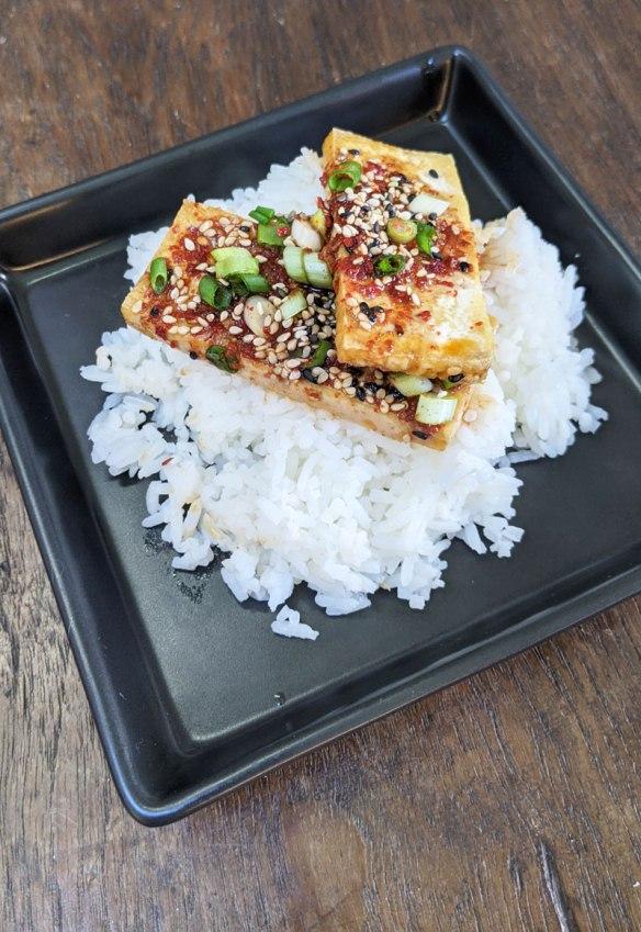 A Korean dish of spicy braised tofu, called Dubu Jorim, sits atop some steamed Jasmine Rice on a square black plate.