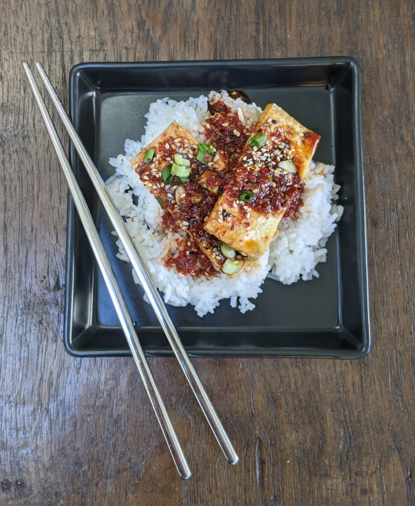 A Korean dish of spicy braised tofu, called Dubu Jorim, sits atop some steamed Jasmine Rice on a square black plate. Metal chopsticks sit on the edge of the plate.