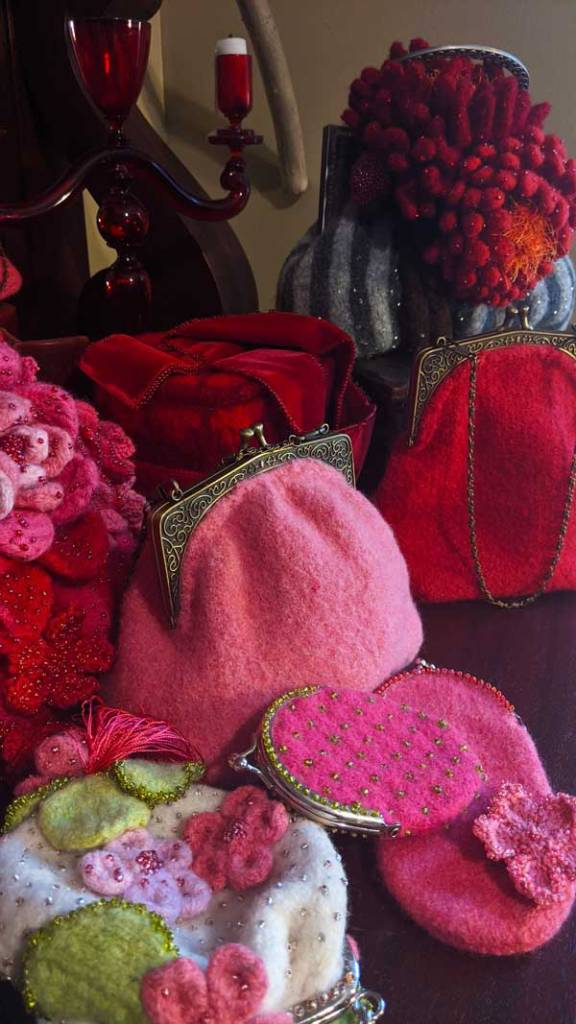 Several felted bags designed by Nora J. Bellows of Noni Designs are arranged together: they are all shades of pink and red. Some have bold red or pink felted flowers.