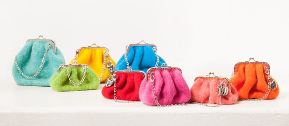 An array of rainbow-colored Lipstick and Change purses sits against a white background.