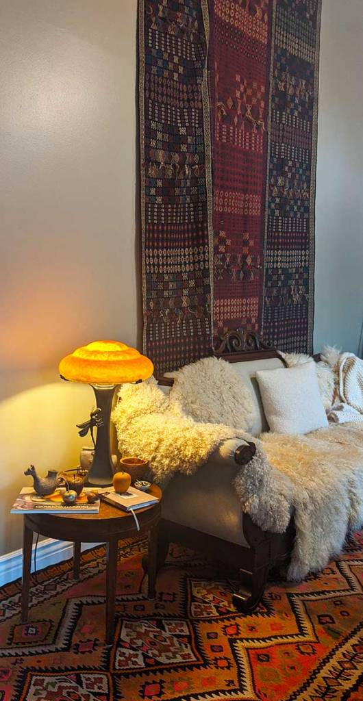 An antique couch with white upholstery and white sheep skins sits empty. Next to it, a small table is covered with books and carved fruit. A unique light sits on the table.