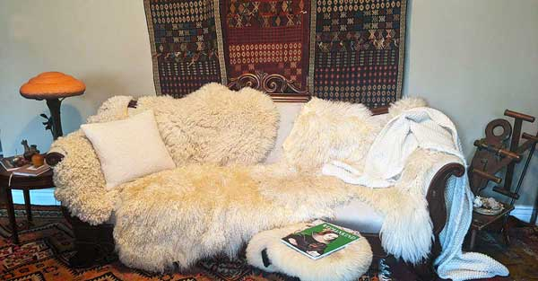 An antique couch covered with sheep skins is centered in the photograph. Behind the couch is a wall tapestry that is shades of red and blue and black.