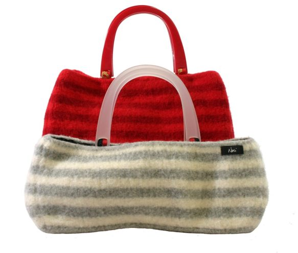A medium sized, red-striped felted bag with red plastic handles sits behind a shorter white and grey striped felted bag with frosted white handles.