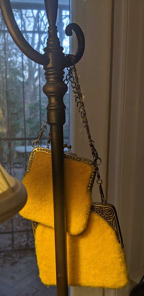 Yellow felted purses hang from an antique floor lamp. The garden is visible through french doors behind the lamp.