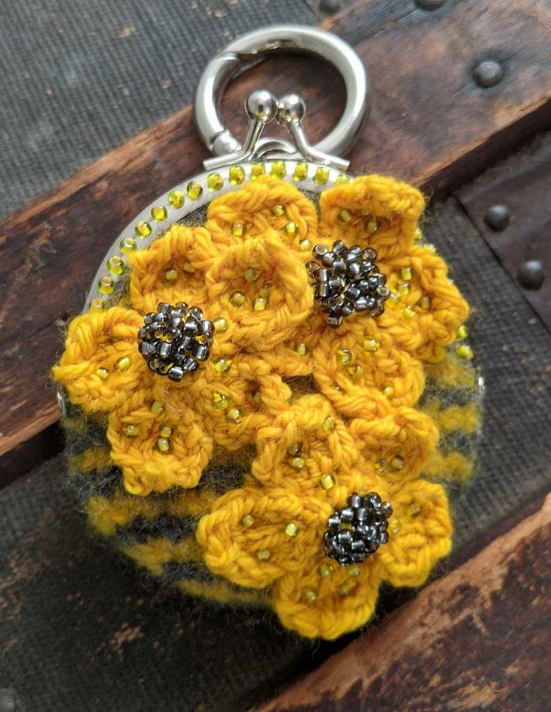 This tiny yellow and grey striped felted purse is decorated with yellow cherry blossom (knitted) flowers with grey beaded centers.