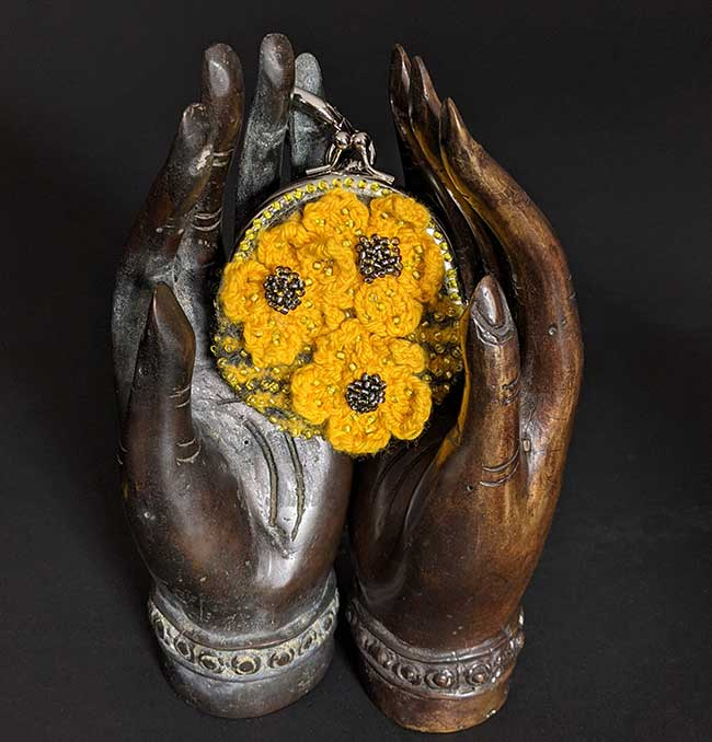 Two metal hands sit on a black surface. Cradled in the metal hands is a small, yellow and grey striped (knitted and then felted) purse that has been hand-beaded and then decorated with yellow knitted flowers.